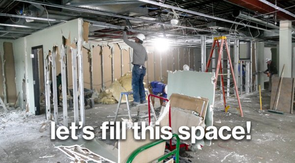 """A man holding onto a beam over his head, in the middle of a partially-demolished ReStore. White text at the bottom says """"let's fill this space!"""""""