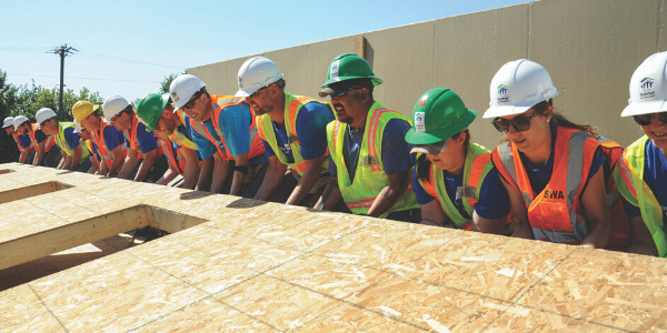 A group of volunteers working together to raise a wall.