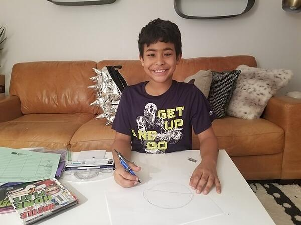 Ayden drawing a picture on the coffee table in front of his couch.