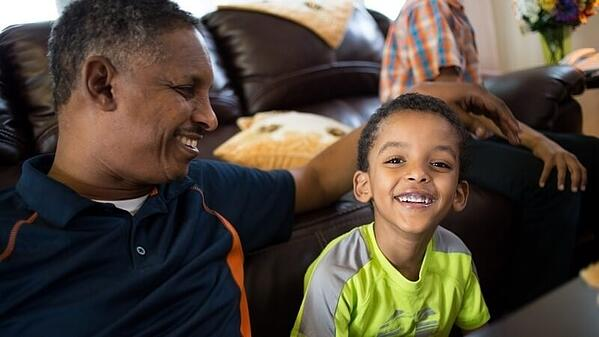 Ahmed and his son in their living room.