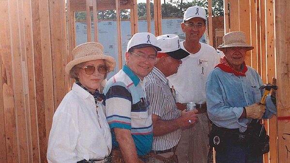 Kenny posing with President Jimmy Carter and two other volunteers inside of a partially-framed house.