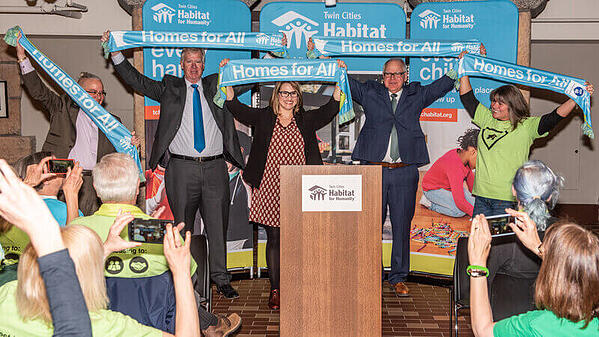 """Leaders and housing advocates holding """"Homes for All"""" banners at Habitat on the Hill 2019."""