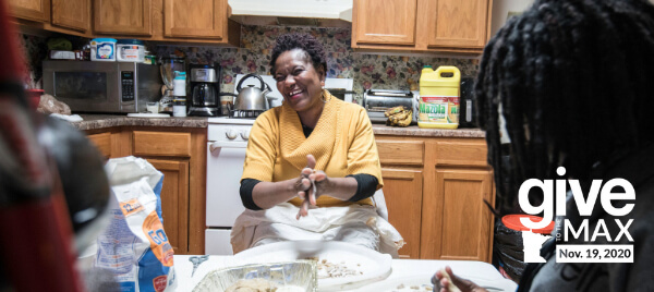 Melo, wearing a yellow sweater, laughing in her kitchen with one of her children in the foreground. They are baking in the center of the kitchen.