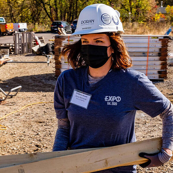 Anne Behrendt, CEO and President of Doran Companies, in a gray EXPO t-shirt with a name tag, gloves, a white hard hat, and a black mask while carrying wooden beams in the sunlight.