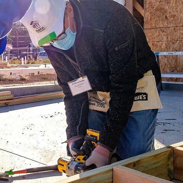 Doug Baker, CEO of Ecolab and Co-Chair for CEO Build 2020, in a gray sweater, jeans, glasses, hard hat, tool pouch, gloves, and a surgical mask, as well as a name tag. He's leaning down to use a power tool on the joint of two wood pieces.