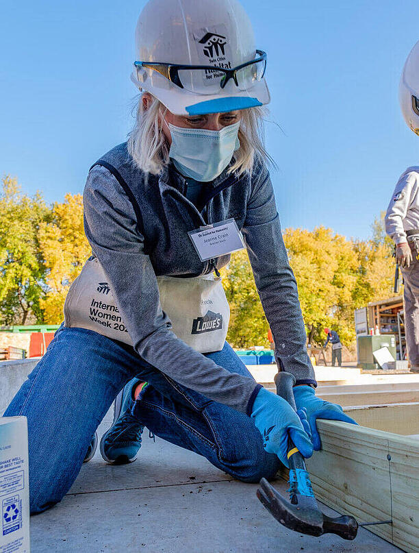 Jeanne Crain, CEO of Bremer Bank, in a gray shirt and vest, jeans, a hard hat, name tag, tool pouch, and gloves. She's outdoors, kneeling down to hammer the joint of two wooden pieces.