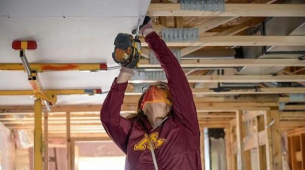 Joan Gabel, President of the University of Minnesota, wearing a maroon and gold UMN sweatshirt, an orange mask, and glasses, reaching above her head to install ceiling drywall with a power screwdriver.