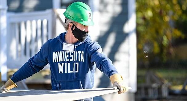 Matt Majka, President and Alternate Governor of the Minnesota Wild, in a blue Minnesota Wild sweatshirt, green hard hat, name tag, black mask, and gloves, carries a sheet of drywall outside.