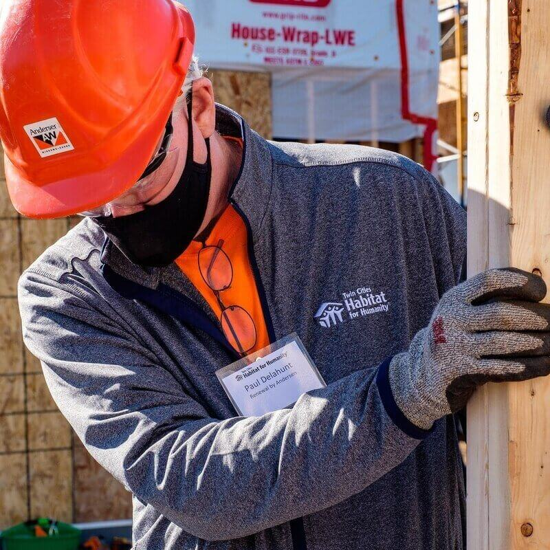 Paul Delahunt, President of Renewal by Andersen & Twin Cities Habitat Board Member, in an orange t-shirt, TC Habitat zip-up sweater, name tag, an orange hard hat, safety goggles, a black mask, and gloves, moving wooden beams outside in the sunlight.