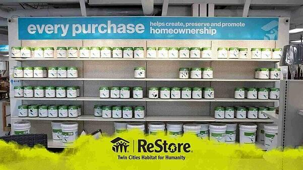 "A shelf of white paint cans with a green stripe at the top. A blue sign is attached to the top of the shelf saying ""every purchase helps create, preserve and promote homeownership"". Floating on top of the image at the bottom is a yellow banner which looks as though it's been painted like clouds, with a black ReStore logo in the center."