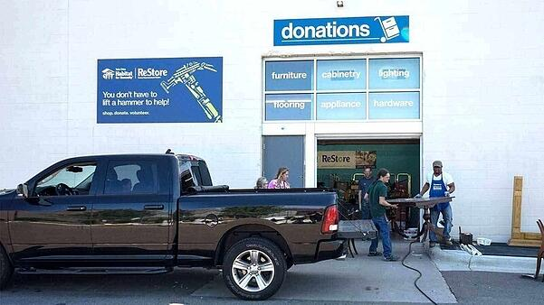 "A black pickup truck in front of the donation door at ReStore. Above the door is a blue ""donations"" sign with white text and a white image of a dolly with boxes on it. Six windows, two high and three across, are below the sign and above the door. Each window has white text. Clockwise from top left: ""furniture"", ""cabinetry"", ""lighting"", ""flooring"", ""appliance"", ""hardware"". Directly above the truck is a blue sign with the Habitat and ReStore logos, plus a hammer comprised of different tools, and the text ""You don't have to lift a hammer to help! shop. donate. volunteer."" A ReStore employee in a blue apron helps a customer move a table into the truck while others watch."