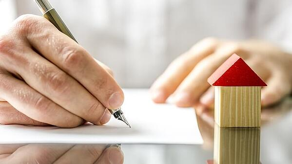 Brightly lit, and on a reflective table, one hand writing on a sheet of white paper with a fountain pen, with the other hand resting on the edge of the paper. A small square wooden block sits next to the paper, with a red triangle on top to form the shape of a house.