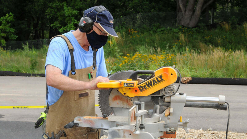 volunteer standing outdoors in a light blue shirt, tan overalls, blue baseball cap and a black mask, wearing ear protection while using a power saw.