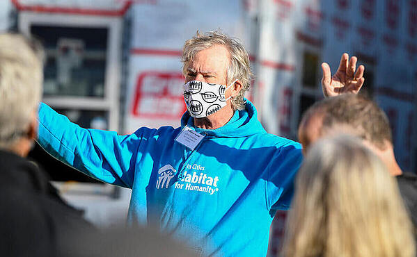 Chris Coleman, CEO of Twin Cities Habitat for Humanity, speaking to a crowd, arms raised to emphasize his point, in front of an in-progress house, wearing a light blue TC Habitat sweatshirt, a white name tag, and a white mask with a black print on it.