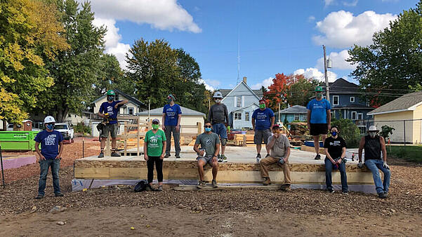 Eleven volunteers standing and sitting on a recently-constructed floor at a build site between several houses.