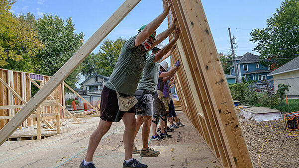 Five volunteers working together to push a wall up into place on as they frame a house.