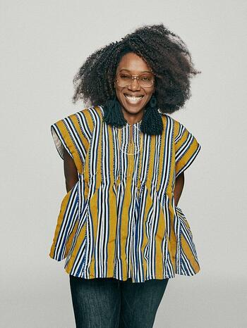 Ethelind Kaba, Campaign Council Member, smiling with her arms behind her, wearing glasses, oversized navy tassel earrings, and a yellow, white, and navy striped oversized blouse. She's standing in front of a light gray background.