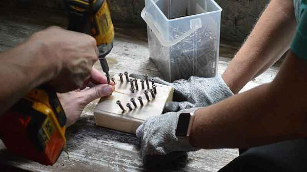 On a wooden floor, nails are being screwed into a block of wood in a heart shape by two people who are out of frame except for their arms. The one on the right has gray work gloves and a smartwatch. A clear plastic box of screws is visible above the block of wood.