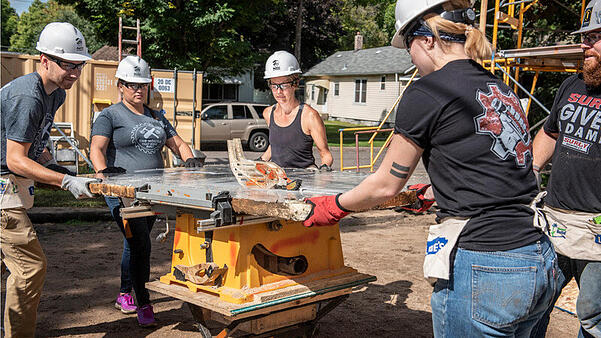 Five volunteers around a saw, splitting a fiberglass sheet. Two are wearing black Surly Gives a Damn t-shirts, two are wearing gray House that Beer Built t-shirts, and one woman is wearing a black tank top. All are wearing hard hats and work gloves, with tool pouches and safety goggles.