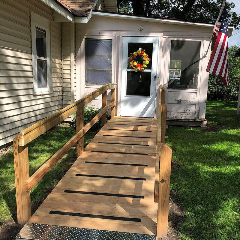 The new wooden mobility ramp leading from the driveway to Larry's front door, which has a wreath with yellow and red flowers on it. To the right hangs an American flag.