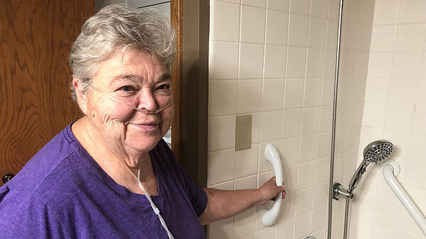 Linda smiling in a purple shirt in her bathroom, showing off her new shower grab bars and handheld shower head.