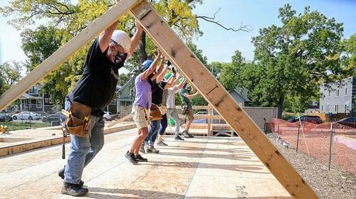Volunteers raising a wall.