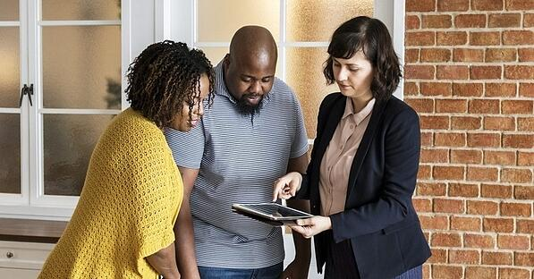 A couple looking at a tablet with a Realtor.