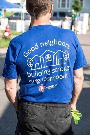 "A man wearing a blue t-shirt saying ""Good neighbors building strong neighborhoods, Republic Services"""