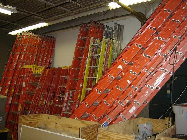 Multiple ladders in the warehouse.