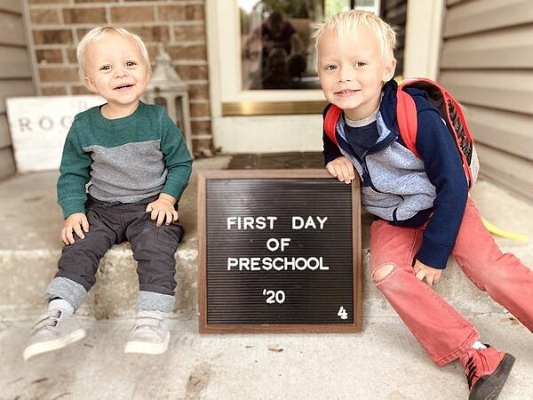 """The Rogness kids on their front steps with a sign saying """"First day of preschool '20."""""""