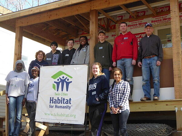 High school students in front of an in-progress home build.