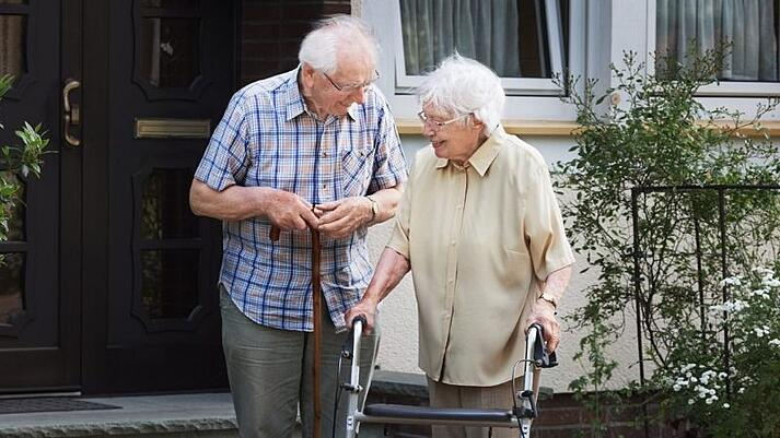 A couple outside of their home with mobility tools.