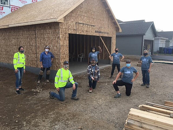 A group of volunteers celebrating progress on a garage.