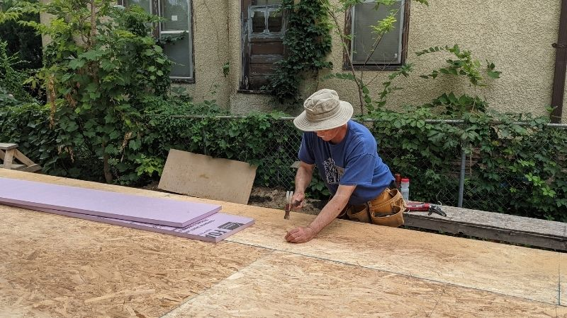 John DeWolf pounds nails at the GV Gone Local build site, fastening subfloor onto first floor trusses.