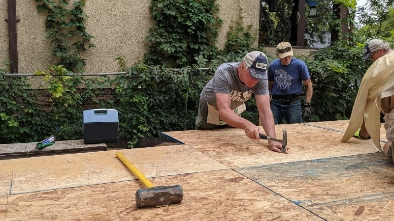 Chris Coleman and other GV Gone Local volunteers work on subfloor installation at 3238 Vincent Ave N.