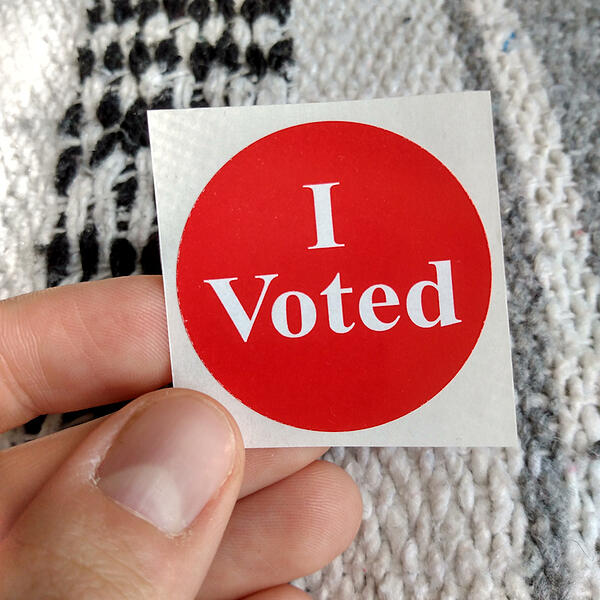 """A red """"I voted"""" sticker being held in front of a gray, white, and black striped knit blanket."""