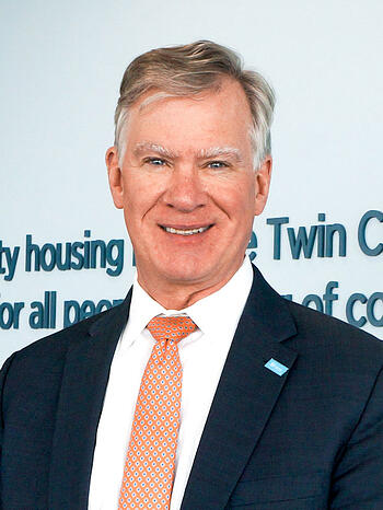 Chris Coleman smiling and standing in front of blue text on a white wall that shows the TC Habitat mission statement. Wearing a dark suit with a light blue Habitat pin, white shirt, and peach tie with a small pattern on it..