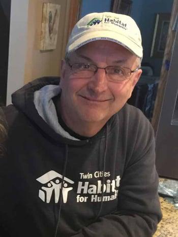 Lou Cristan, Board Member, smiling in his home wearing a gray TC Habitat sweatshirt, glasses, and a white TC Habitat baseball cap