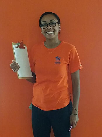 Mari Ojeda smiling and standing in front of an orange background while holding a clipboard in one hand. She's wearing glasses, earrings and a necklace with two small bracelets, an orange TC Habitat shirt, and dark pants. In her other hand she holds a pen, and a nametag is clipped to her left hip.