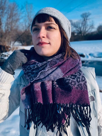 Polina Montes de Oca outside in the snow and looking off into the distance, wearing a light gray hat and vest, darker gray gloves, a white cable knit sweater, and a purple and gray leopard-print scarf.