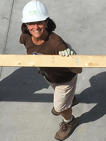 Sharon Mason, standing on concrete below the camera and looking up and smiling. Wearing a brown t-shirt, khaki shorts, work boots, gloves, a white hard hat, and glasses. She's holding a wooden beam.
