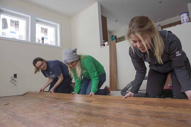 Allie laying flooring at a Habitat build site