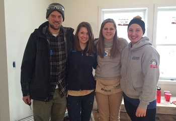 AmeriCorps members posing for a photo in an in-progress house.