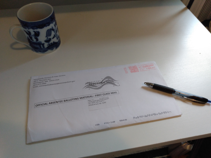 On a white desk, an official absentee ballot envelope, with a black pen lying on top of it. There's a white mug with blue designs on it in the upper left corner of the desk.