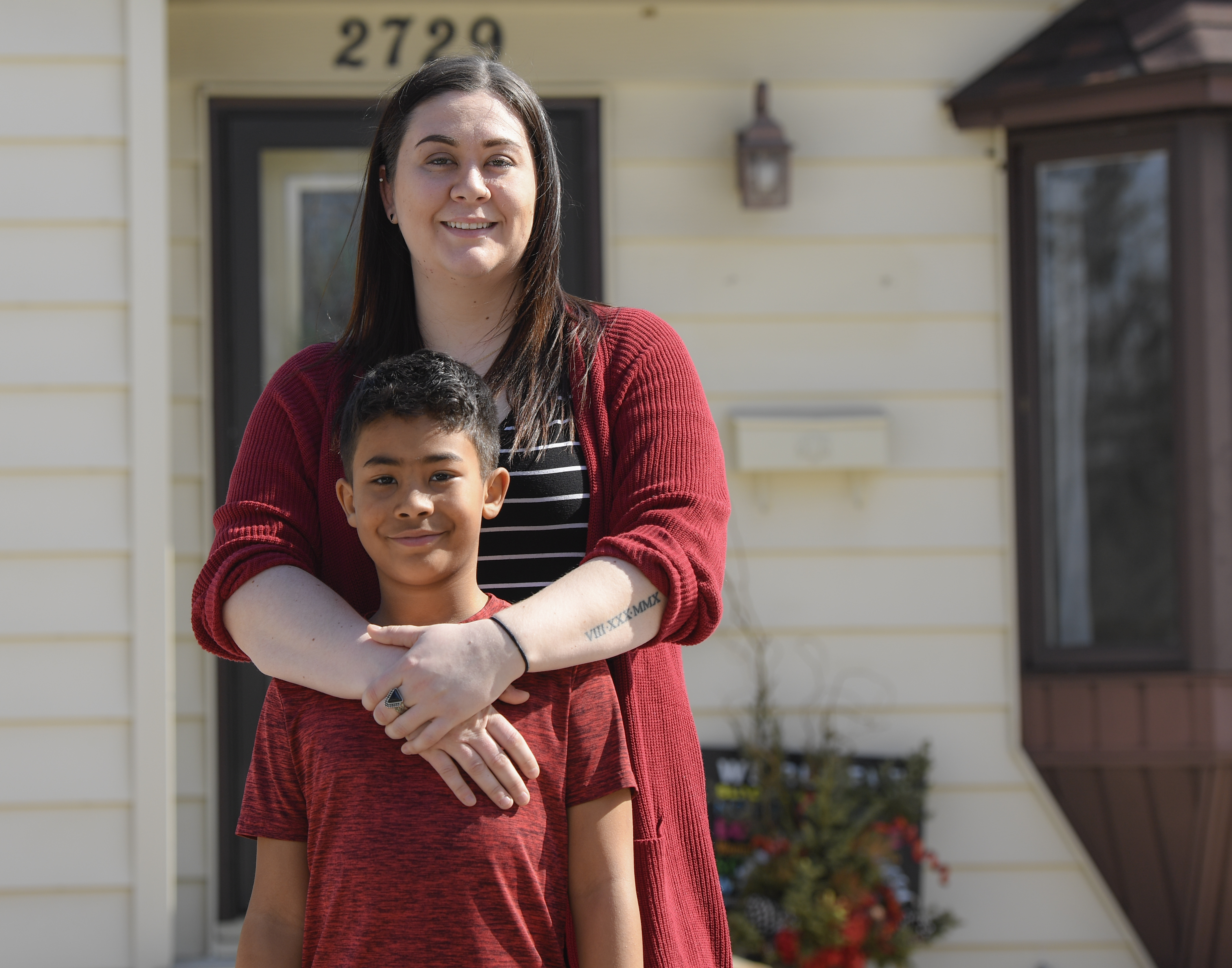 Brittany and Ayden in front of their home