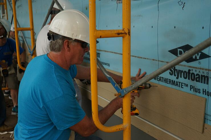 Chris Coleman, President & CEO of Twin Cities Habitat, installing some siding.