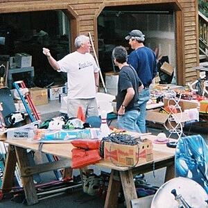 Dennis in a white shirt and khakis in front of his garage, gesturing with one arm. Two men in blue shirts and jeans (one in a baseball cap) stand listening to him. Surrounding them on the driveway are multiple tables covered in boxes and miscellaneous items for donation to ReStore.