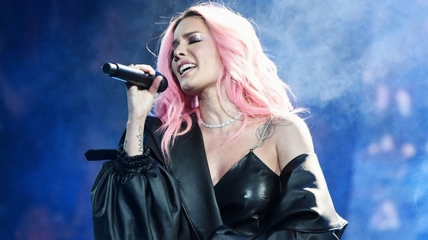 Singer Halsey performing in a black outfit with pink hair.
