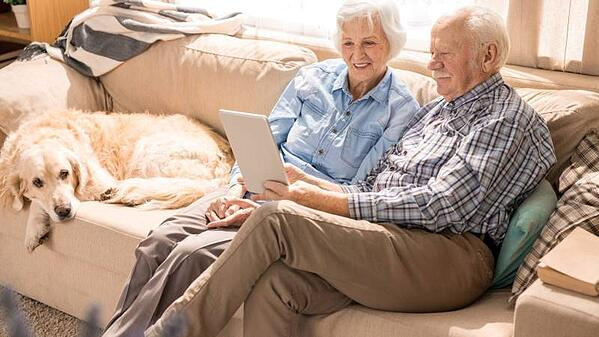 Health Implications of Moving as a Senior - husband and wife using tablet on couch – TC Habitat