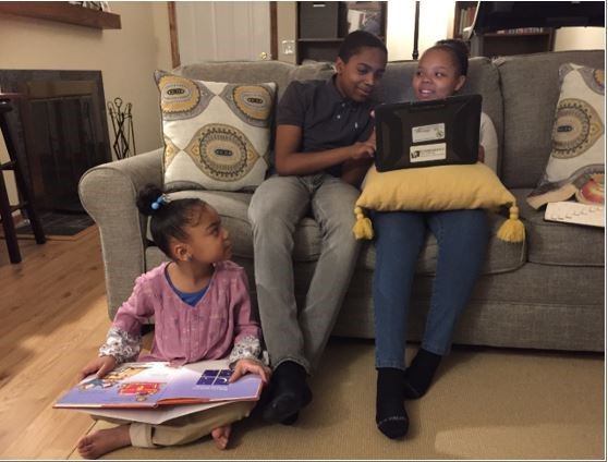 Don helping his sister with homework on the couch while his younger sister looks up at them from the floor, holding a book.